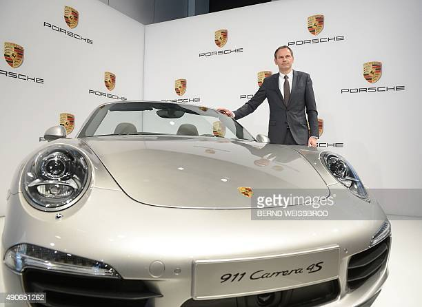 Picture taken on March 15 2013 shows Oliver Blume then board member of German sports car maker Porsche posing next to a Porsche 911 Carrera 4S car...