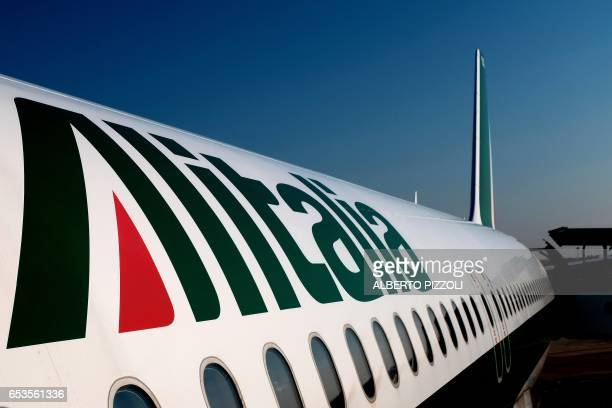 A picture taken on March 15 2017 shows an Alitalia Etihad plane on the runway of the airport of Brindisi / AFP PHOTO / ALBERTO PIZZOLI