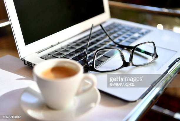 Picture taken on March 15, 2020 shows glasses on a laptop at a home office desk in Salzburg, Austria. / Austria OUT