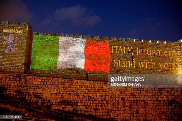 Picture taken on March 15, 2020 shows the Italian flag projected on the walls of the ramparts of Jerusalem's Old City in show of support for those...