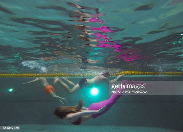 A picture taken on March 16 2017 shows a woman practicing swimming with a mermaid tail at a mermaid training school in a pool in Moscow Russian women...
