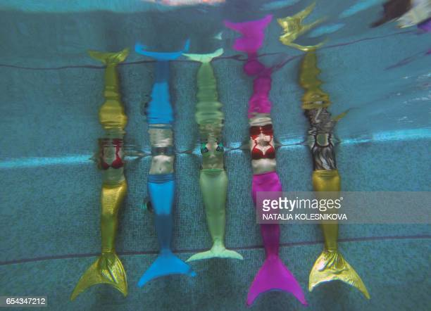 TOPSHOT A picture taken on March 16 2017 shows women practicing swimming with mermaid tails at a mermaid training school in a pool in Moscow Russian...