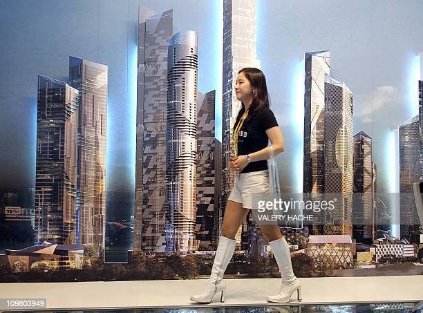 CHARCOSSEY A picture taken on March 17 2009 at Cannes' Palais des festivals shows an hostess walking in front of a scale model during the 21st...