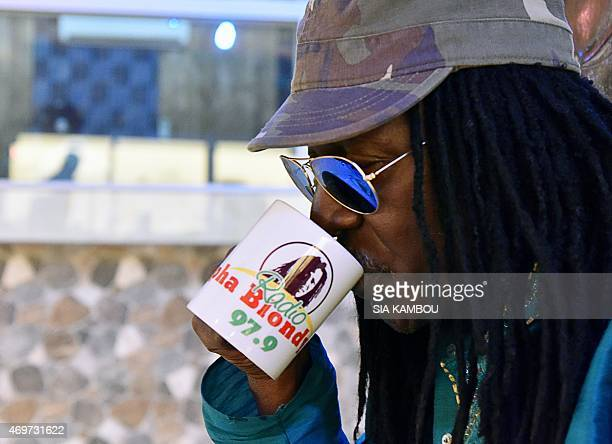 A picture taken on March 17 2015 shows Ivorian reggae Alpha Blondy drinking from a mug during an interview at his radio station Alpha Blondy FM in...