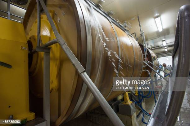 A picture taken on march 17 2015 shows the rotation of wooden churns under the control of a worker in the butter manufacture in Echire central...