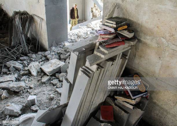 A picture taken on March 17 at the site of a reported airstrike on a mosque in the village of AlJineh in Aleppo province shows books about Islamic...