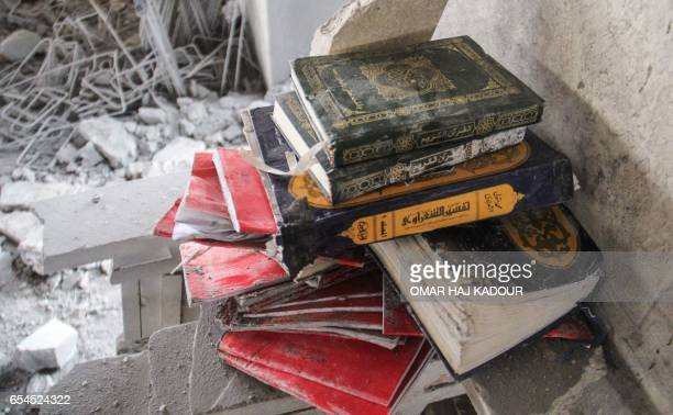 A picture taken on March 17 at the site of a reported airstrike on a mosque in the village of AlJineh in Aleppo province shows copies of the Koran...