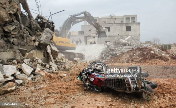 A picture taken on March 17 at the site of a reported airstrike on a mosque in the village of AlJineh in Aleppo province shows a damaged motorcycle...