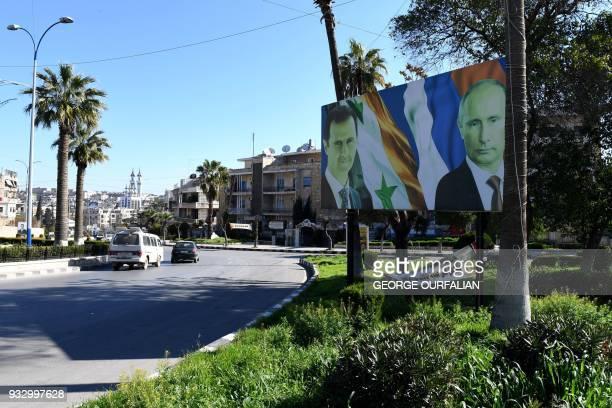 Picture taken on March 17 shows portraits of Russian President Vladimir Putin, Syrian President Bashar al-Assad and Lebanese Hezbollah Leader Hassan...