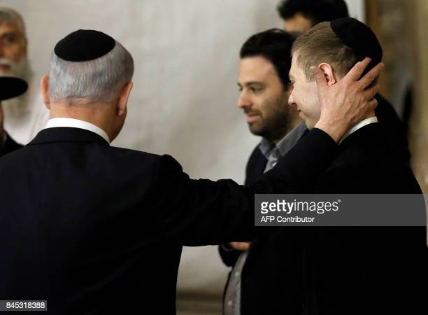 A picture taken on March 18 2015 shows Israeli Prime Minister Benjamin Netanyahu and his son Yair visiting the Wailing Wall in Jerusalem The son of...