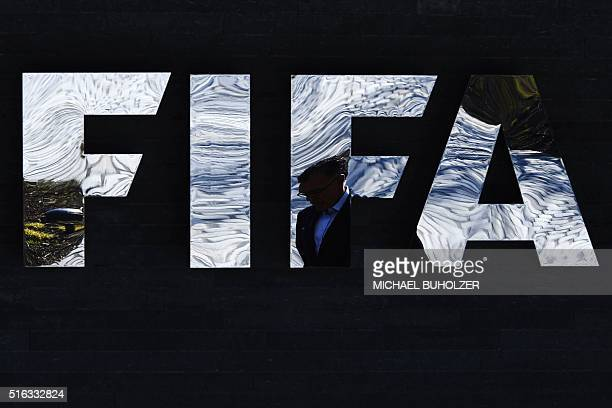 A picture taken on March 18 2016 shows a man walking past a FIFA logo at the FIFA headquarters in Zurich FIFA's new president Gianni Infantino faces...