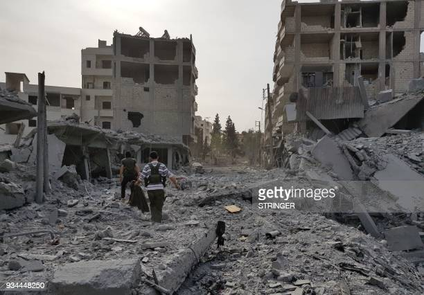 TOPSHOT A picture taken on March 19 2018 shows young men walking amid the destruction in the Syrian Kurdish city of Afrin a day after Turkishled...