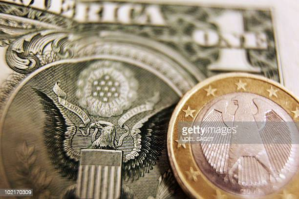 A picture taken on March 2 2010 in Paris shows a one euro coin displayed in front of a one dollar note The euro slumped to its lowest level in more...