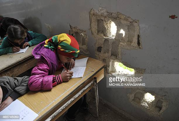 Picture taken on March 2, 2015 shows pupils attending the first day of school in the Syrian Kurdish town of Kobane, also known as Ain al-Arab, as...