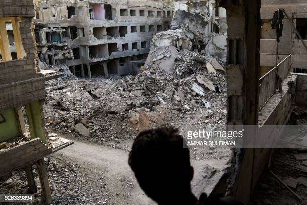 TOPSHOT A picture taken on March 2 2018 shows a Syrian youth looking through a balcony from a severely damaged building at the exposed painted walls...