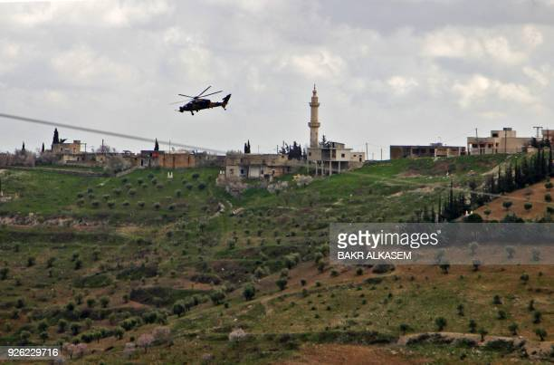 A picture taken on March 2 2018 shows a Turkish army T129 ATAK attack helicopter flying towards the village of AlMaabatli in the Afrin region in the...