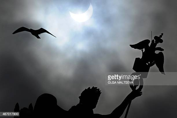A picture taken on March 20 2015 shows a partial solar eclipse over the Arc of the General Staff building in St Petersburg AFP PHOTO / OLGA MALTSEVA