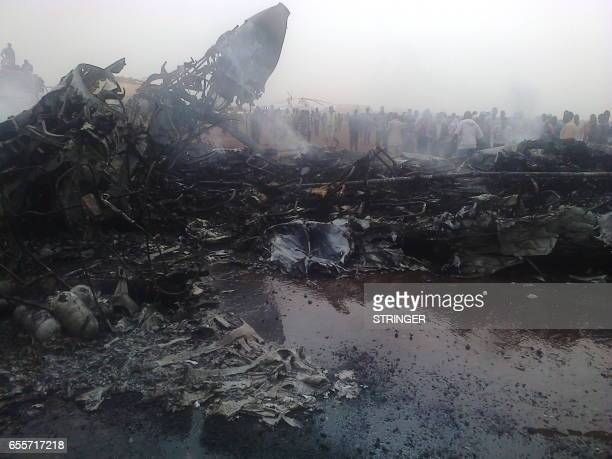Picture taken on March 20, 2017 in South Sudan's northwestern city of Wau shows people gathering near a plane wreckage after a jet crash-landed,...