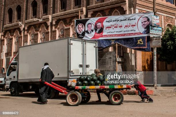 A picture taken on March 20 2018 shows a poster supporting Egyptian President Abdel Fattah alSisi hanging in a street in the city of Sohag south of...