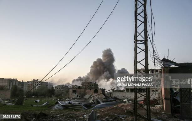 A picture taken on March 20 2018 shows smoke plumes billowing in the Eastern Ghouta enclave town of Hammuriyeh on the outskirts of the capital...