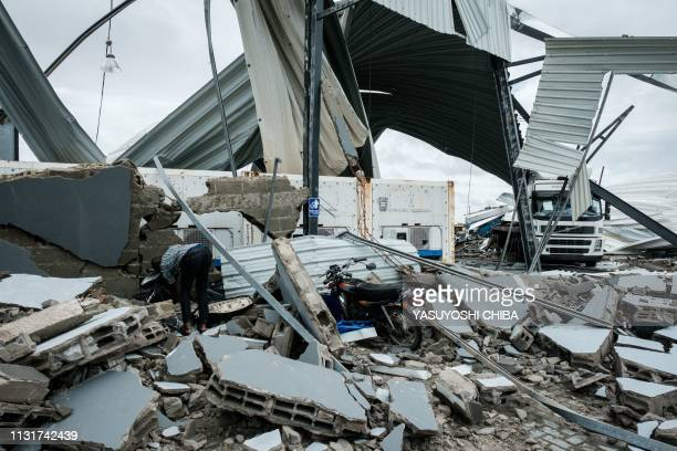 A picture taken on March 20 2019 shows the broken part of the building of a logistics company after a strong cyclone hit Beira Mozambique Five days...
