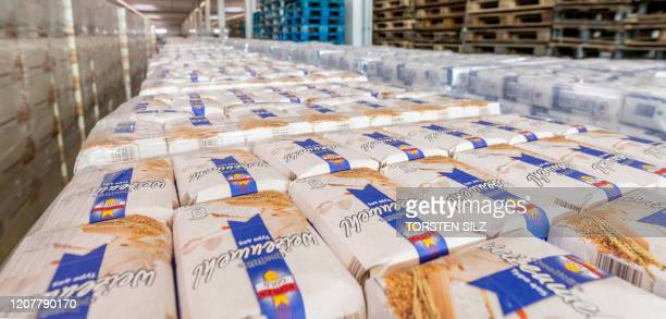 Picture taken on March 20, 2020 shows piles of flour packets at the central logistics warehouse of discounter Aldi-Sued, in Bingen, western Germany....