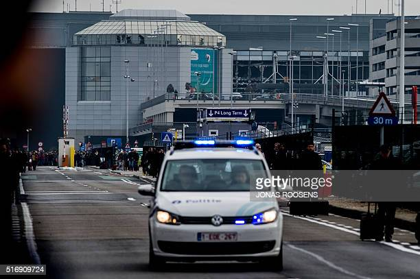 A picture taken on March 22 2016 shows a Belgian police vehicle driving past passengers who are evacuating the Brussels Airport of Zaventem At least...