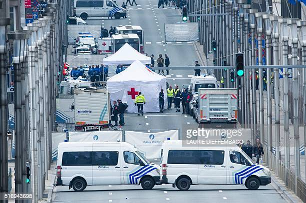 Picture taken on March 22, 2016 shows Red Cross tents and police vehicles at the Wetstraat - Rue de la Loi, which was evacuated after an explosion at...