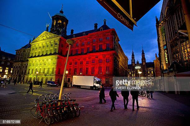 A picture taken on March 22 2016 shows the Royal Palace at Dam Square in Amsterdam displaying the colors of the Belgian flag in tribute to the...