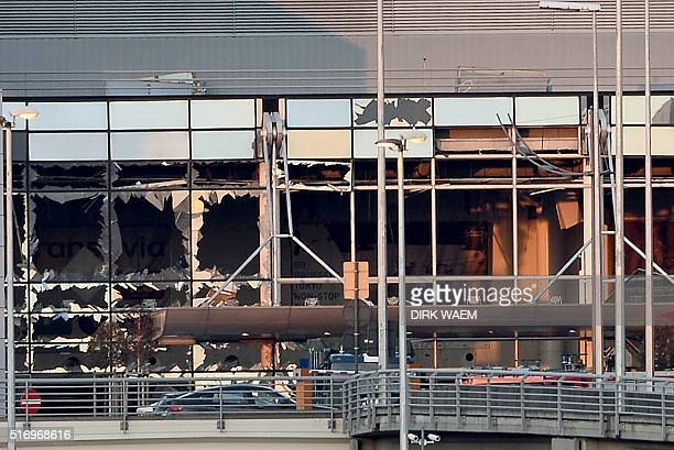 A picture taken on March 22 2016 shows the shattered glass facade of the departure hall of Brussels Airport in Zaventem following twin blasts Around...
