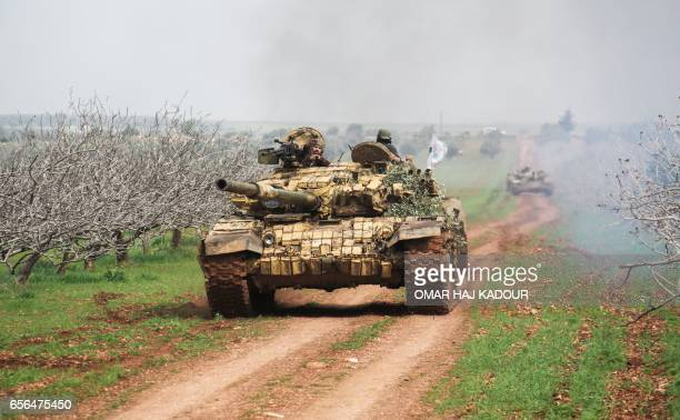 A picture taken on March 22 2017 near the town of Maardes in the countryside of the central Syrian province of Hama shows a rebel tank driving down a...