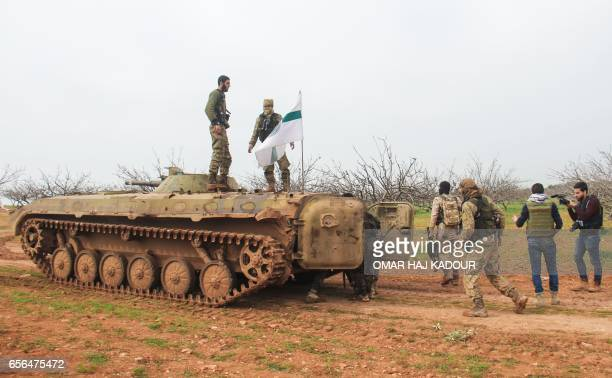 A picture taken on March 22 2017 near the town of Maardes in the countryside of the central Syrian province of Hama shows rebel fighters walking past...