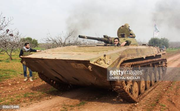 A picture taken on March 22 2017 near the town of Maardes in the countryside of the central Syrian province of Hama shows a rebel armoured vehicle...