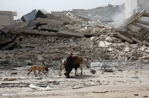 TOPSHOT A picture taken on March 22 2018 shows a man walking with a loaded donkey and followed by a dog past the rubble of a destroyed building in...