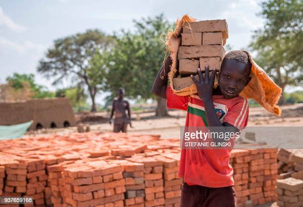 A picture taken on March 22 shows children carrying bricks to an oven near Nyamlel South Sudan Child labour has been on the rise in South Sudan a...
