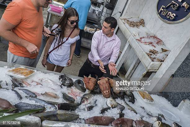 A picture taken on March 23 2016 shows tourists looking at a selection of fish and sea food at a restaurant in Egypt's coastal resort of Sharm...