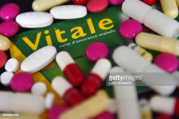 A picture taken on March 23 2017 in Nantes western France shows pills tablets suppositories and pharmaceutical drugs on a Carte Vitale the electronic...