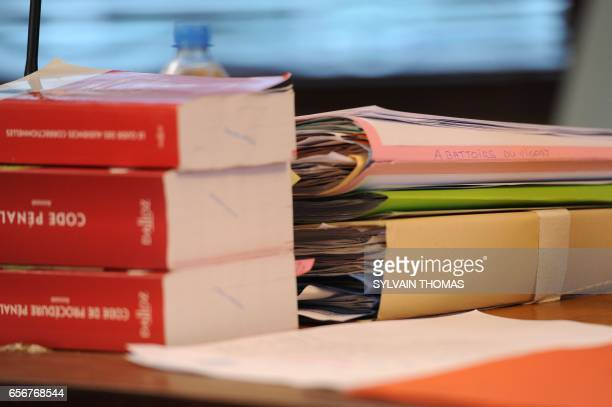 A picture taken on March 23 2017 shows folders and penal codes lying on a table prior to the start of the trial of three employees working in the...