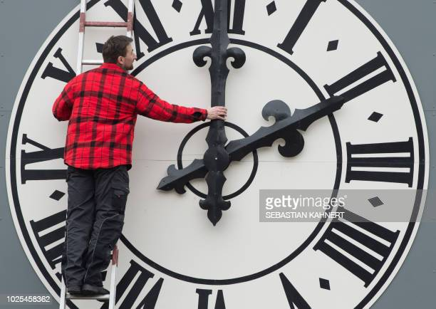 Picture taken on March 23 2018 shows a technician working on the clock of the Lukaskirche Church in Dresden eastern Germany The European Commission...
