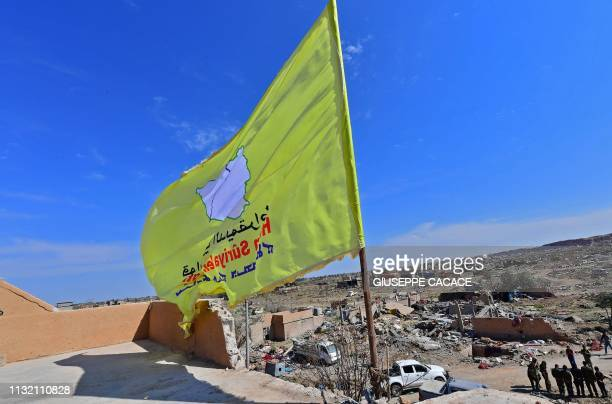 Picture taken on March 23, 2019 shows the US-backed Syrian Democratic Forces' flag atop a building in the Islamic State group's last bastion in the...