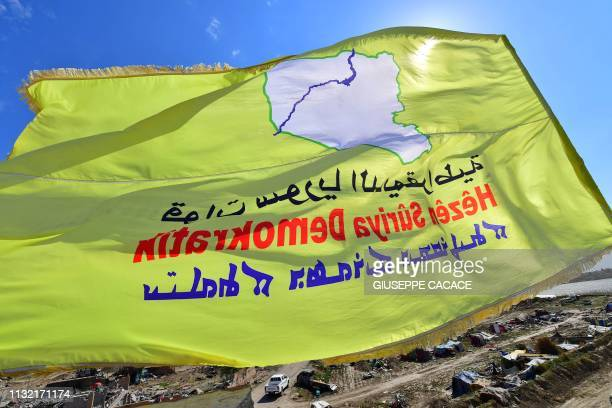 A picture taken on March 23 2019 shows the USbacked Syrian Democratic Forces' flag atop a building in the Islamic State group's last bastion in the...
