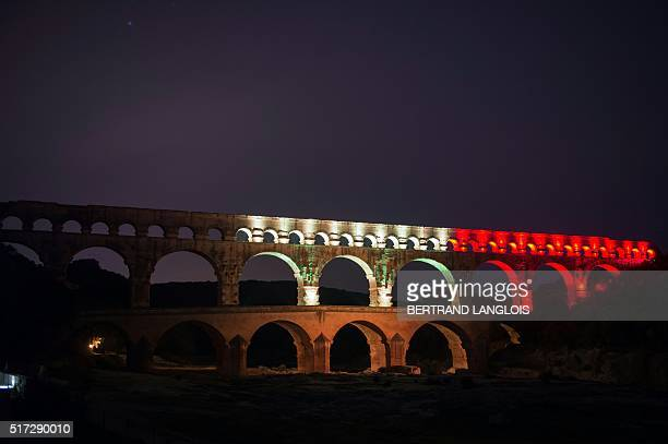 Picture taken on March 24, 2016 in Remoulins, southern France, shows the Pont du Gard , a Roman era aqueduct circa 19 BC, illuminated in colours of...