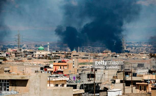 A picture taken on March 24 2017 shows smoke plumes rising in a neighbourhood in west Mosul during an offensive by the Iraqi forces to retake the...