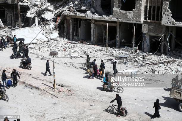 A picture taken on March 25 2018 shows people preparing to evacuate from the town of Arbin in the Eastern Ghouta region on the outskirts of the...