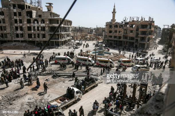 TOPSHOT A picture taken on March 25 2018 shows Syrian Red Crescent ambulances waiting as people prepare to evacuate from the town of Arbin in the...