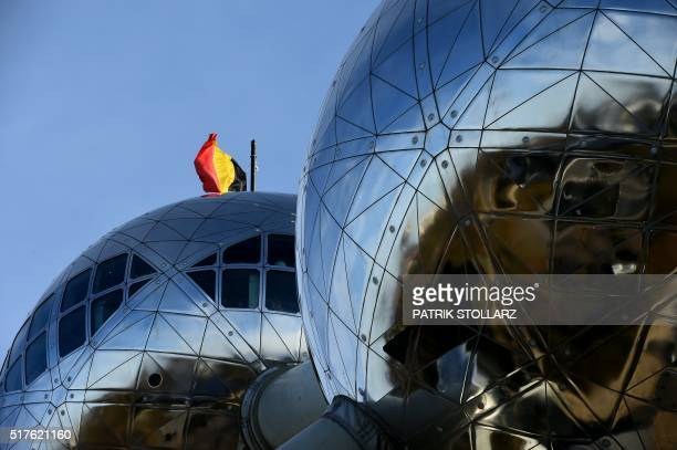 A picture taken on March 26 2016 in Brussels shows the atomium with the Belgian flag at halfmast / AFP / PATRIK STOLLARZ