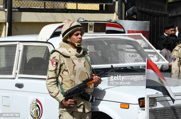 A picture taken on March 26 2018 shows an Egyptian army conscript standing guard outside a polling station in the capital Cairo on the first day of...