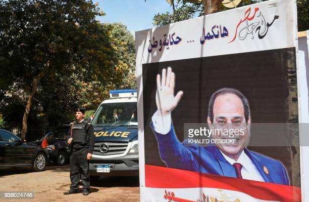 A picture taken on March 26 2018 shows Egyptian policemen standing guard outside a polling station with an electoral banner depicting incumbent...