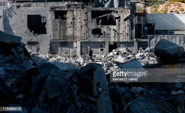 TOPSHOT A picture taken on March 26 shows a Palestinian man making his way through the rubble of a building in Gaza City after Israeli air strikes...