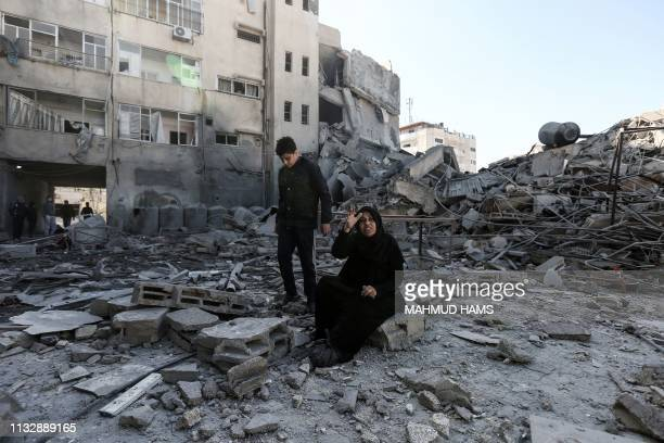 TOPSHOT A picture taken on March 26 shows a Palestinian woman sitting next to the rubble of a building in Gaza City after Israeli air strikes hit...